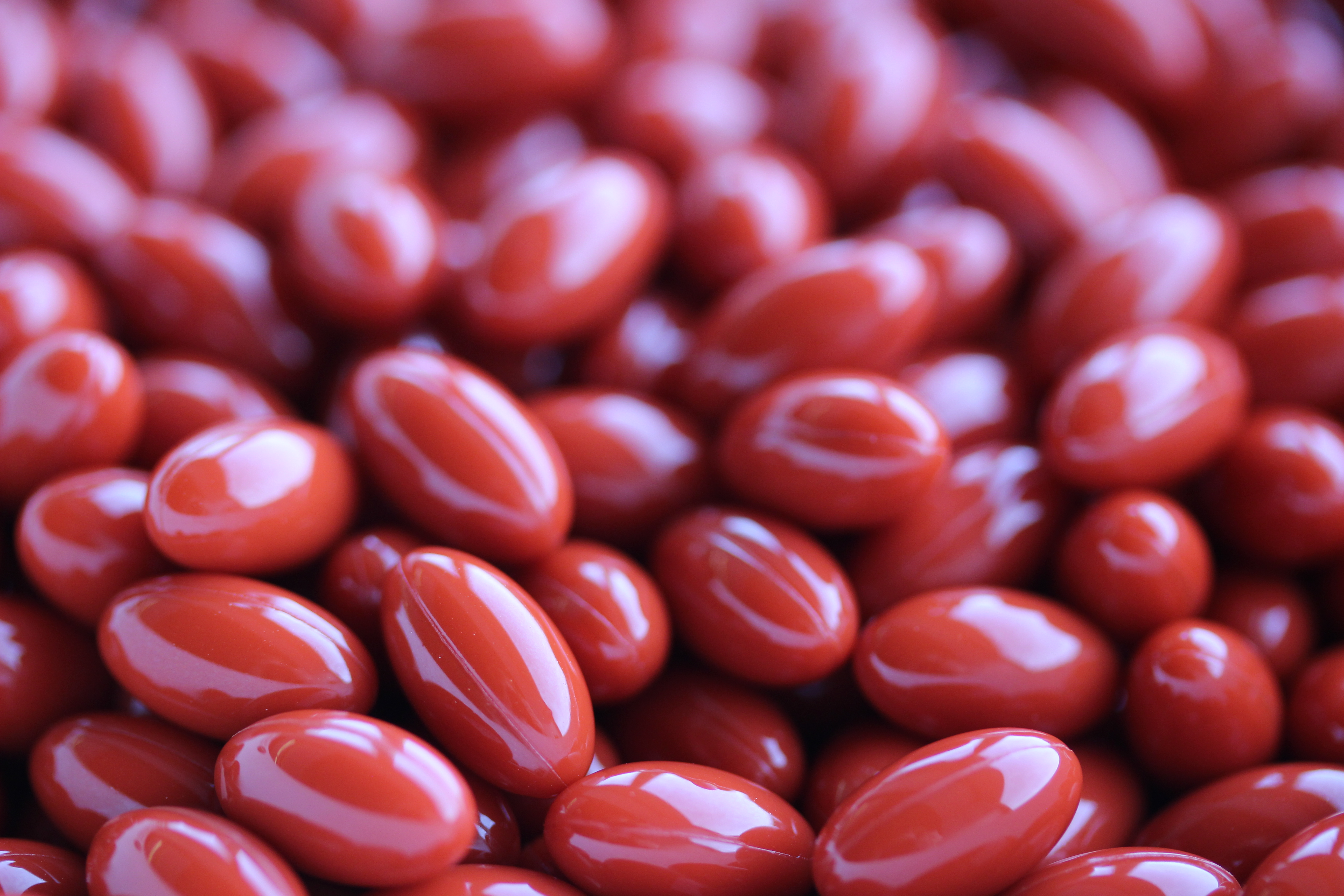 large quantities of red colored softgels